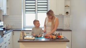 Eine junge schöne kaukasische Mutter mit Koch des weißen Haares und des Sohns in einer hellen Küche Mutter unterrichtet Sohn zu k stock footage