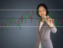 Eine junge schöne Geschäftsfrau, die ein Diagramm zeichnet Lizenzfreies Stockfoto
