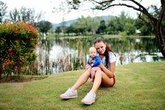 Eine junge schöne Mutter hält ein kleines Baby stockbilder