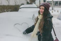 Eine junge schöne stilvolle Frau malt ein Herz auf einem schneebedeckten lizenzfreies stockfoto
