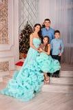 Eine junge schöne vierköpfige Familie in den eleganten Kleidern mit einem Hund stehen zu Hause, aufwerfend nahe dem Baum des neue lizenzfreie stockfotografie