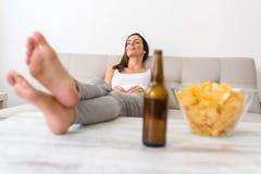 Eine junge Schönheit, die auf einem Sofa mit Bier und Kartoffel sich entspannt Stockbild