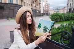 Eine junge Schönheit in einem eleganten Hut sitzt auf einer Bank in einer neuen Wohnnachbarschaft und liest ein Papierbuch Sie sc Lizenzfreies Stockfoto