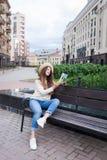 Eine junge Schönheit in einem eleganten Hut sitzt auf einer Bank in einer neuen Wohnnachbarschaft und liest ein Papierbuch Sie sc Lizenzfreie Stockfotografie