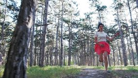 Eine junge Schönheit läuft glücklich entlang die Straße unter zahlreichen Kiefern Langsame Bewegung stock footage