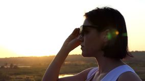 Eine junge schlanke Frau steht mit Sonnenbrille in ihren Händen bei Sonnenuntergang in Slo-MO stock video footage