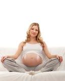 Eine junge schwangere Frau, die auf einem Sofa sitzt Lizenzfreie Stockfotografie
