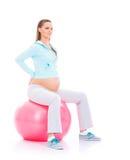 Eine junge schwangere Frau, die mit einem Eignungsball ausarbeitet Stockbilder