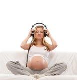 Eine junge schwangere Frau, die Musik hört Stockbilder