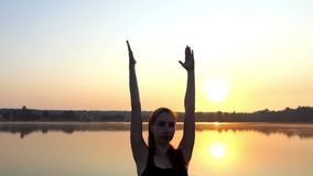 Eine junge schwangere Frau tut eine Yoga-Baum-Übung bei einem herrlichen Sonnenuntergang stock footage