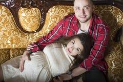 Eine junge schwangere Frau und ihr glücklicher Ehemann, die auf dem couc stillstehen lizenzfreie stockfotografie
