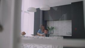Eine junge spanische Mutter mit ihrem Sohn, der am Tisch sitzt, unterrichtet, um das Kind zu lesen, das seinem Sohn hilft und auf stock video