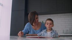 Eine junge spanische Mutter mit ihrem Sohn, der am Tisch sitzt, unterrichtet, um das Kind zu lesen, das seinem Sohn hilft und auf stock video footage