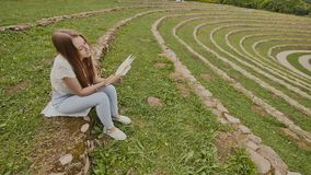 Eine junge Studentin liest ein Buch, das auf dem Gras unter einem großen Stadion sitzt Vorbereitung für Studie stock video