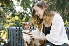 Eine junge tausendjährige Frau hat einen zarten Moment mit ihrem Schoßhund stockfotos