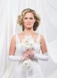 Eine junge und attraktive blonde Braut in einem weißen Kleid Lizenzfreies Stockfoto
