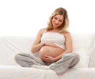 Eine junge und glückliche blonde schwangere kaukasische Frau Stockbild