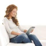 Eine junge und glückliche Frauenlesung auf einem Tabulator Lizenzfreies Stockbild