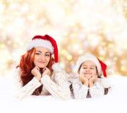 Eine junge und glückliche Mutter und eine Tochter auf einem Weihnachtshintergrund Stockfotografie