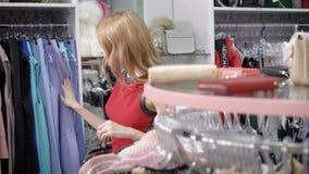 Eine junge und hübsche Frau, die im Einkaufszentrum wie shopaholic Blicke Kleidung auf Aufhängern, die Dame betrachtet, schaut st stock video footage