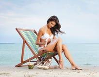 Eine junge Frau in einem weißen Badeanzug, der Sonnencreme addiert Lizenzfreie Stockfotos