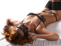 Eine junge und reizvolle Redheadfrau, die in Wäsche legt Lizenzfreies Stockfoto
