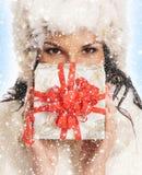 Eine junge und schöne Frau, die ein Geschenk anhält lizenzfreies stockbild