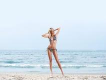 Eine junge und sexy blonde Frau, die auf dem Strand aufwirft Stockfoto