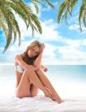 Eine junge und sexy blonde Frau, die auf einer Rücksortierung sich entspannt Stockfotografie