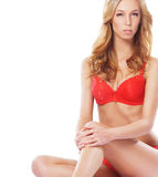 Eine junge und sexy blonde Frau, die in der roten Wäsche aufwirft Stockfotos