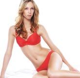 Eine junge und sexy blonde Frau, die in der roten Wäsche aufwirft Lizenzfreies Stockbild