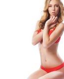 Eine junge und sexy blonde Frau, die in der roten Wäsche aufwirft Lizenzfreie Stockbilder