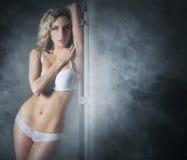 Eine junge und sexy blonde Frau, die in der weißen Wäsche aufwirft Stockbild