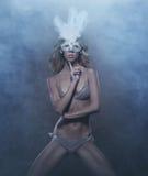 Eine junge und sexy blonde Frau in einer weißen Maske Stockfoto