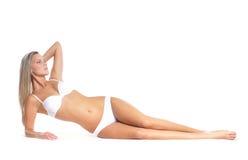 Eine junge und sexy Frau, die in einen Badeanzug legt Stockfotos