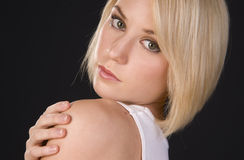 Junge vibrierende blonde Frau schaut über ihrer Schulter im Headshot Stockfotos