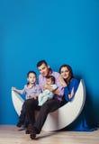 Eine junge vierköpfige Familie, die auf dem sichelförmigen Mond auf Blaurückseite sitzt Stockfotos