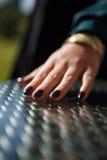 Eine junge weibliche Hand mit dunklem glittery Nagellack Stockbild