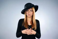Eine junge Witwe im schwarzen Kleid mit einem Hut Stockfoto