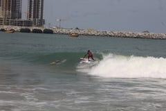Eine Jungenfahrt auf den Kamm von Wellen in Lagos-Strand, Bewunderer schauen an lizenzfreies stockfoto
