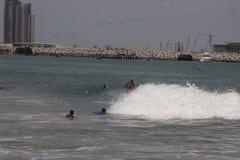 Eine Jungenfahrt der Kamm von Wellen in Lagos-Strand, Bewunderer schauen an stockfotos