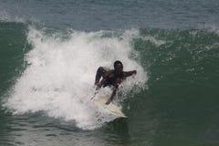 Eine Jungenrolle hinunter den Kamm von Wellen in Lagos-Strand, Bewunderer schauen an lizenzfreie stockbilder