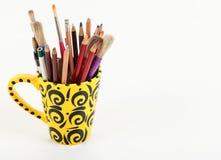 Eine künstlerische gelbe Schale mit Kunstversorgungen Stockbild