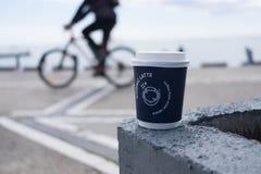 Eine Kaffeetasse mit einem Radfahrer im Hintergrund stockbild