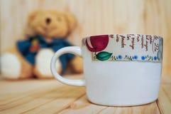 Eine Kaffeetasse mit Teddybären und hölzernem Hintergrund Abbildung der roten Lilie Lizenzfreies Stockbild