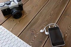 Eine Kamera, eine Tastatur, ein intelligentes Telefon auf einem dunklen Schreibtisch Stockfotografie