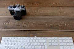 Eine Kamera und eine Tastatur auf einem dunklen Schreibtischhintergrund Lizenzfreies Stockbild