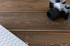 Eine Kamera und eine Tastatur auf einem dunklen Schreibtischhintergrund Lizenzfreies Stockfoto