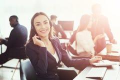 Eine kaukasisch-aussehende Frau betrachtet in die Kamera dem Büro stockfotos