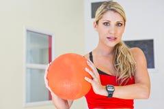 Eine kaukasische Frau, welche die Eignung hält einen Ball ausübt Lizenzfreies Stockbild